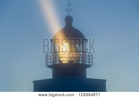 Strong light beam from old lighthouse tower in the fog. Night in Ponta do Pargo, Madeira island.