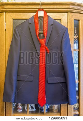 Men's suit hanging on hangers on a sideboard in anticipation.
