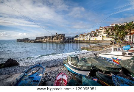Old colorful fishing boats laying on the shore in Camara de Lobos fisherman's village. Popular touristic town in Madeira island, Portugal.
