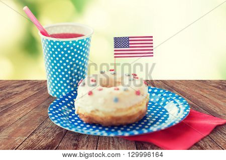 american independence day celebration, patriotism and holidays concept - close up of donut decorated with flag and juice in disposable tableware on wooden table at 4th july party over green background