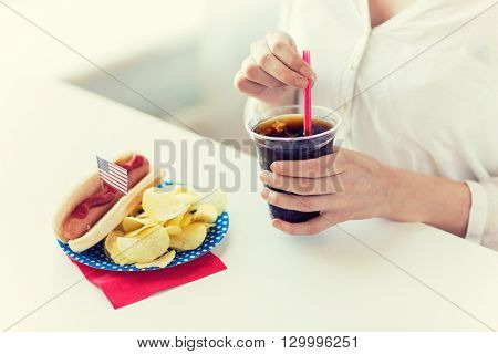 american independence day, celebration, patriotism and holidays concept - close up of woman drinking cola from plastic cup with hot dog and potato chips on 4th july at home party