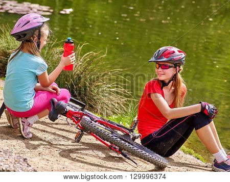 Bikes cycling family. Happy mother and daughter  rides bicycle. Family have  rest near water in park. Kid drinking bottle water. Bicycles are on coast.