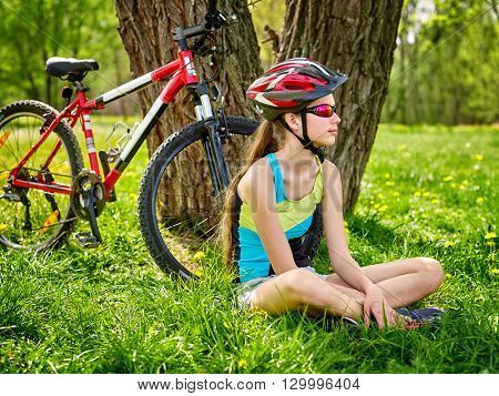 Bikes cycling girl. Girl rides bicycle. Girl in cycling have a rest sitting under tree. Cycling is good for health. Cyclist wearing helmet looking away.