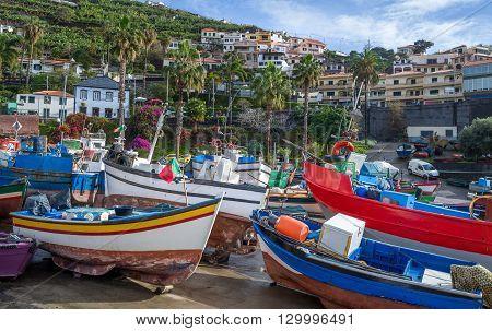 Old colorful fishing boats on the shore. Camara de Lobos village, popular touristic spot at Madeira island.