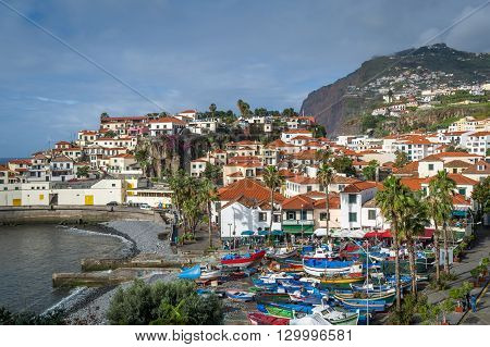 Aerial view to Camara de Lobos town and fishing boats harbor with hills and mountain on the background. Madeira island, Portugal.