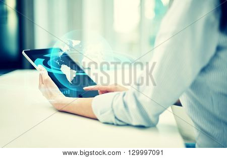 business, technology, communication and people concept - close up of woman with tablet pc computer and globe hologram at office or home