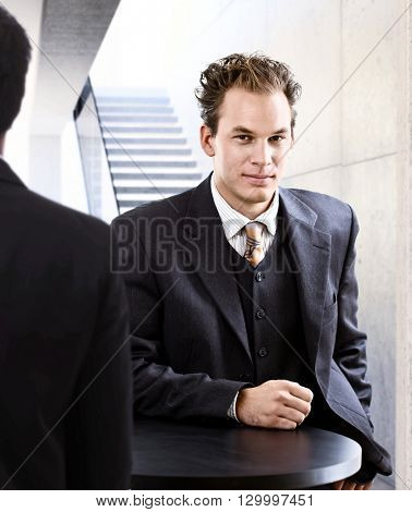 Portrait of elegant young businessman looking at camera.