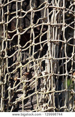 Old fishing net hanging on log as background