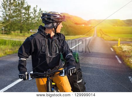 Happy biker on backdrop of mountains in Iceland.