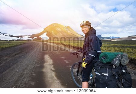 Happy biker on backdrop of lake and snowing mountains
