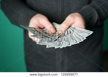 man hand giving 100 dollar bills in studio.