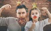 Funny family! Father and his child daughter girl with a paper accessories. Beauty funny girl holding poster