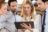 Business people in the office and looking at a digital tablet. Businesswoman holding tablet and shar poster