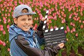 stock photo of clapper board  - Boy in jacket and cap with cinema clapper board in their hands standing on field with tulips - JPG