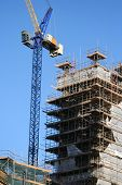 foto of construction crane  - crane and unfinished building surrounded by scaffolding - JPG