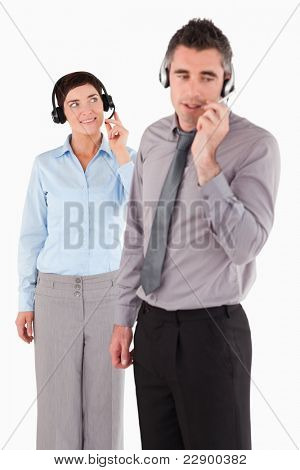 Portrait of coworkers speaking through headsets against a white background