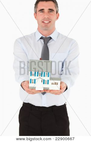 Real estate agent showing a miniature house against a white background
