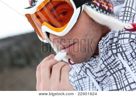 young skier putting cold cream lip stick on his lips