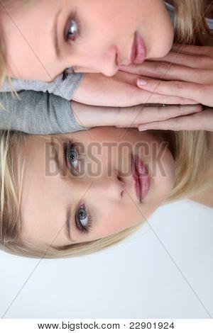 Tiro de estudio de una mujer mirando su reflejo en un espejo