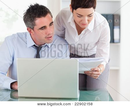 Colleagues comparing a blueprint folder to an electronic one in an office