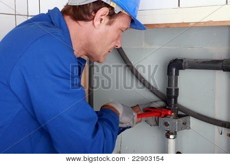 Plumber tightening a joint with a wrench