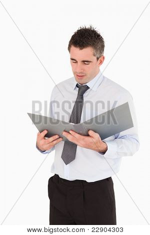 Portrait of a man looking at a binder against a white background