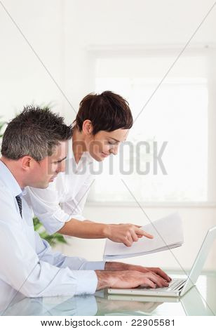 Portrait of colleagues comparing a blueprint folder to an electronic one in an office
