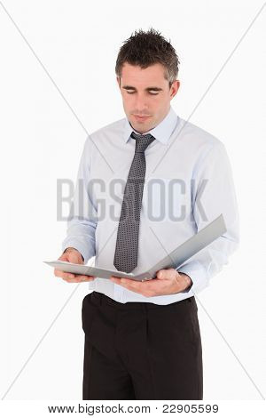 Portrait of a man looking a binder against a white background