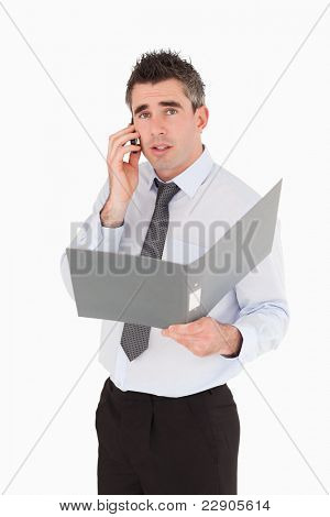 Portrait of a man making a phone call while holding a binder against a white background