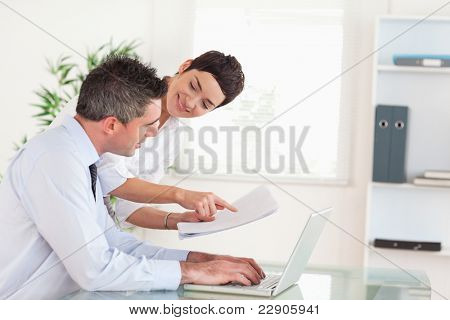 Office workers comparing a blueprint folder to an electronic one in an office
