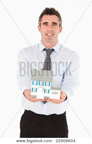Real estate agent holding a miniature house against a white background
