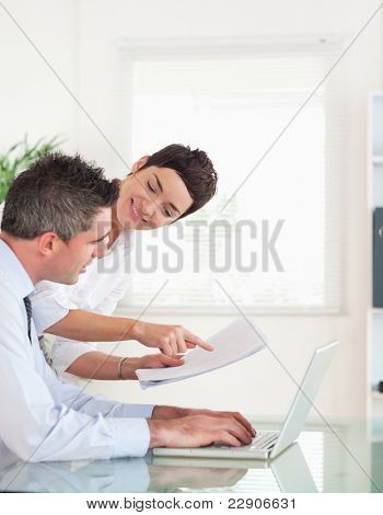 Portrait of coworkers comparing a blueprint folder to an electronic one in an office