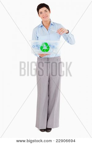 Woman putting a plastic bottle in a recycling box against a white background