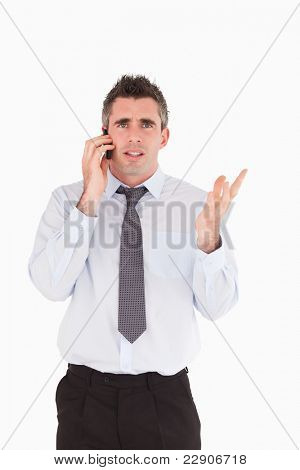 Portrait of a disappointing man making a phone call against a white background