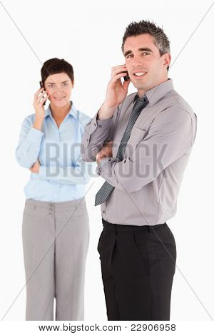 Portrait of coworkers making a phone call against a white background
