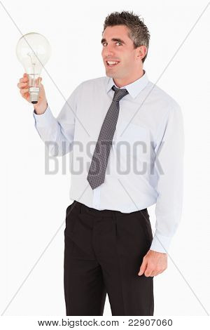 Smiling man holding a light bulb against a white background