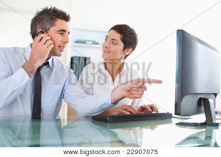 Close up of a man showing something to his coworker on a computer against a white background