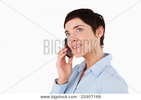 Close up of a serious woman making a phone call against a white background