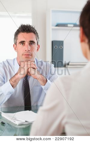 Portrait of a serious manager interviewing an applicant in his office