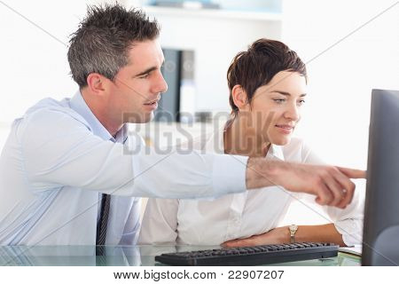 Man showing something to his coworker on a computer in an office