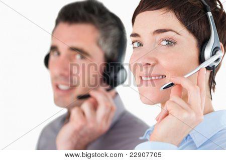 Close-up de operadores de central de portaria, falando através de fones de ouvido contra um fundo branco