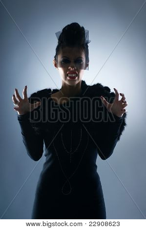 Portrait of female vampire over dark background
