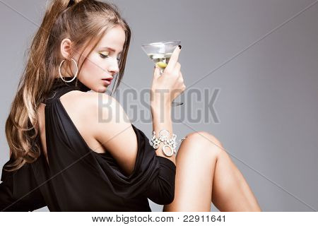 young attractive woman with glass of martini, profile, studio shot