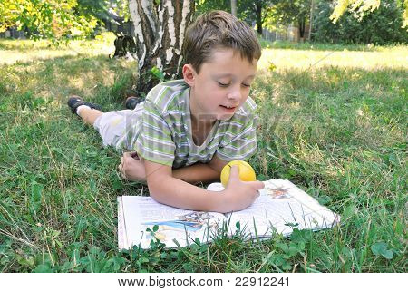 A boy with apple reads book on the grass in public garden