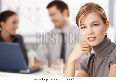 Portrait of young blond businesswoman sitting at table, others chatting behind.?