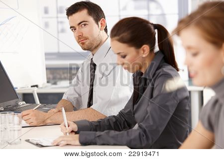 Young office workers having business training, sitting at meeting table, writing notes.?