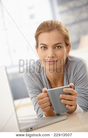 Portrait of happy pretty woman lying on couch with coffee mug and laptop computer, smiling at camera.?