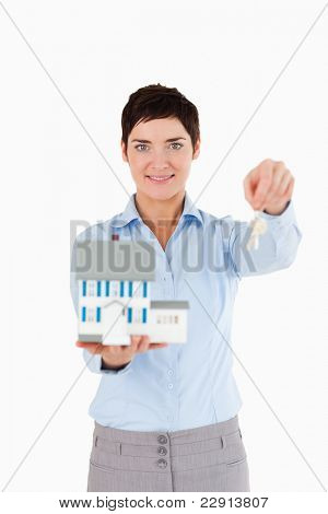 Real estate agent holding keys and a miniature house against a white background