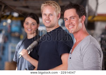 A group of three mechanics in a auto repair shop, looking at the camera