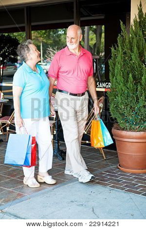 "Senior couple out shopping together.  (word visible in window is just ""sangria"", not restaurant name or logo)"